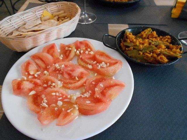 Vegan paella de verduras and tomato salad
