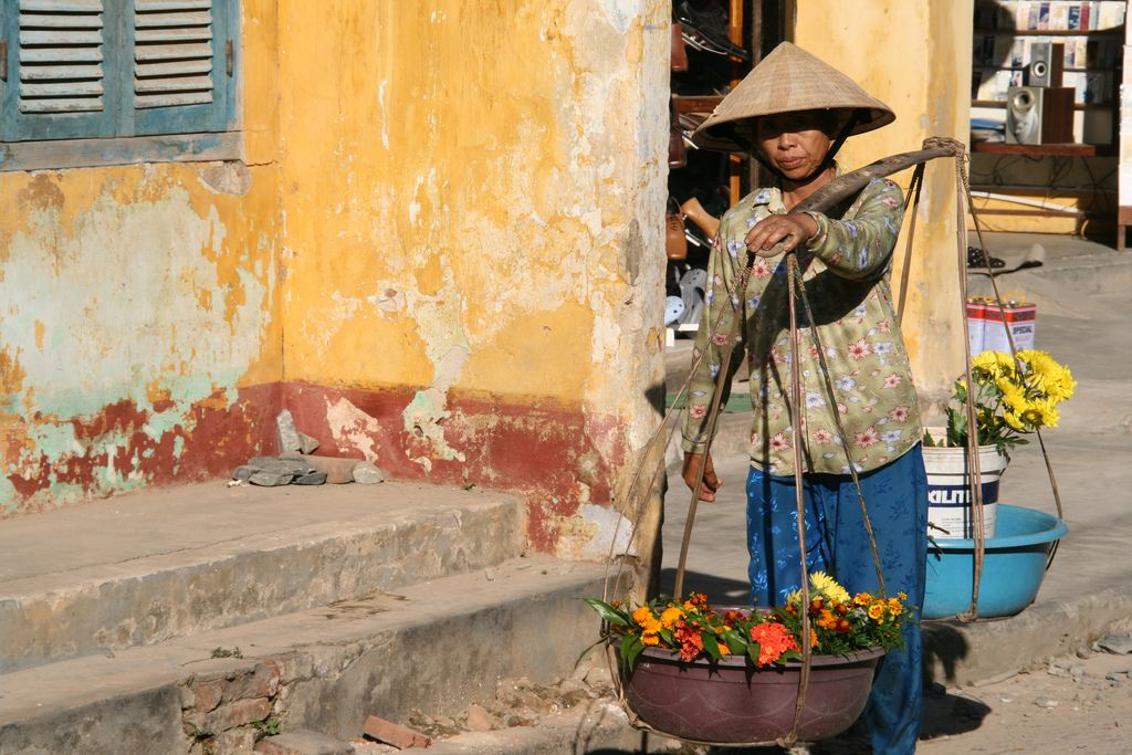 A Vietnamese woman carries flowers through the streets of Hoi An, Vietnam