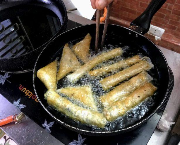 Frying spring rolls in Hanoi vegan cooking class